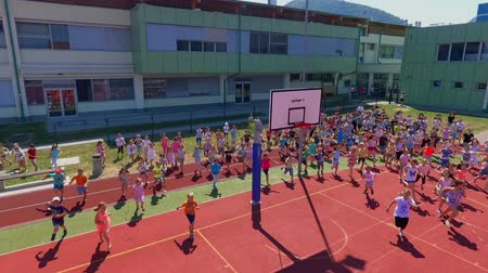 işe : GRIZE, SLOVENIA - 10. JUNE 2017  Children start running across the basketball court. They are having fun and are doing different sports activities. Its summer time. Aerial shot.