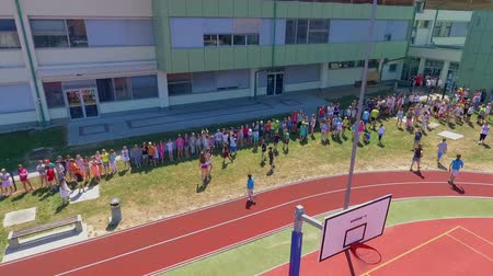 işe : GRIZE, SLOVENIA - 10. JUNE 2017  Its summer time and childen are having a sports day full of different activities. Aerial shot.