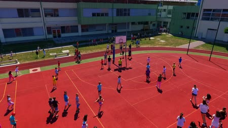 işe : GRIZE, SLOVENIA - 10. JUNE 2017  Children are walking and running across the sport facility. Its summer time. Aerial shot.