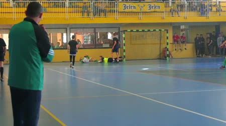 gymnasium : Two soccer players fall on the ground during the match. Thier coach is watching the game. Stock Footage