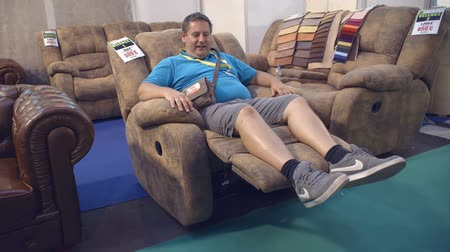 trade show : GORNJA RADGONA, SLOVENIA 28. AUGUST 2017  A visitor of the fair is trying out the armchair and he is really enjoying it. Stock Footage