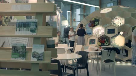 expo : GORNJA RADGONA, SLOVENIA 28. AUGUST 2017  At one of the booths visitors and exhibitors are talking to each other. There are many brochures displayed on the shelves. Stock Footage