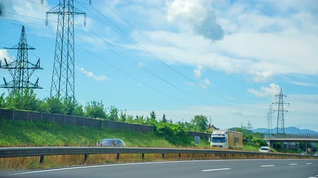 ljubljana : There is electrical wiring over a highway. Cars are driving very fast. Its a very nice summer day.
