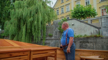 ljubljana : A middle-aged man is standing on the deck of a boat and he is looking at the city. There are also many trees around on both banks of the river. Stock Footage