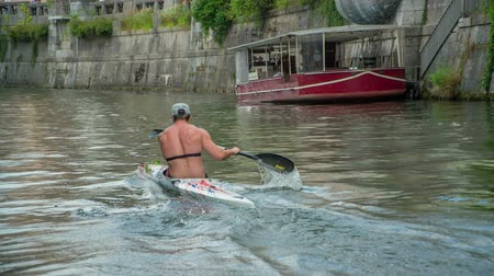 ljubljana : A young man is paddling a kayak across the river of Ljubljanica. He is doing that really fast.