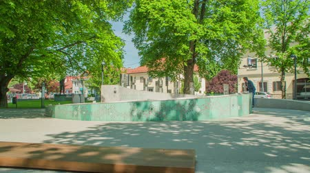 vyhloubení : ZALECCELJE, SLOVENIA - 18. MAY 2017 Benches and beautiful green trees in a park in a small town of ?alec, somewhere in the middle of Slovenia.