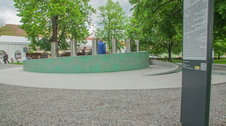 slovenya : ZALEC, SLOVENIA JUNE 10th 2017 A fountain with different kinds of beer is located somewhere in the middle of a green park. A few people are standing there and are enjoying their beer. Stok Video