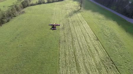 ancinho : A tractor is pulling a big agricultural machinery behind it. Aerial shot. The farmers are preparing hay in summer time.