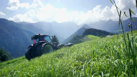 trator : Its a beautiful and sunny day up in the mountains and farmers are busy preparing hay in the summer time.