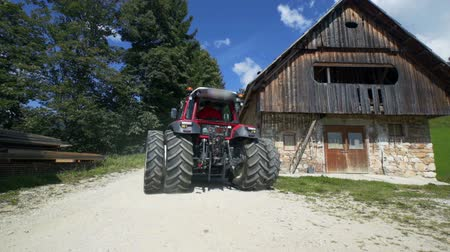 forgó : A red tractor is driving up to the farmhouse. Its a sunny day. The farmer has finished working for today.