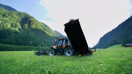 ancinho : A tractor is standing in the middle of a grass field in the Logar Valley and the agricultural machinery is facing the sky.
