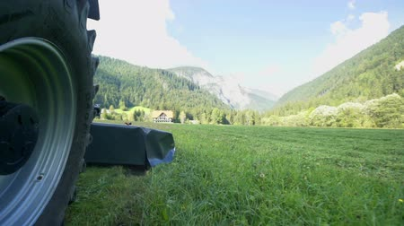 forgó : Farmers are cuting grass with agricultural machinery on a beautiful summer day. The Logar Valley.