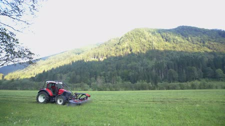 faca : A tractor is driving across a huge grass field and it is cutting grass with agricultural machinery. The Logar Valley is very big and farmers have a lot of work to do.