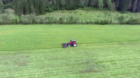 ancinho : A red tractor is slowly driving across the field and its cutting grass. Aerial shot. Its a nice and warm summer day. Vídeos