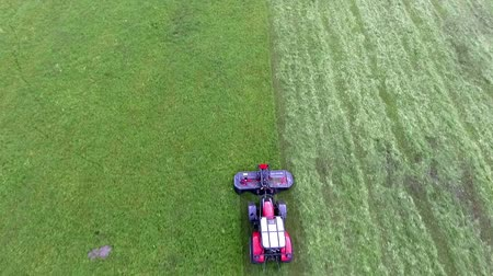 ancinho : A red tractor is driving across the field and its cutting grass with a big agricultural machinery. Aerial shot. Vídeos