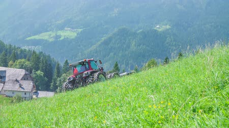 hay mowing : A farmer is driving his tractor on steep hills and he is cutting grass with grass cutting machinery. There is a farm in the valley. The day is sunny and warm.