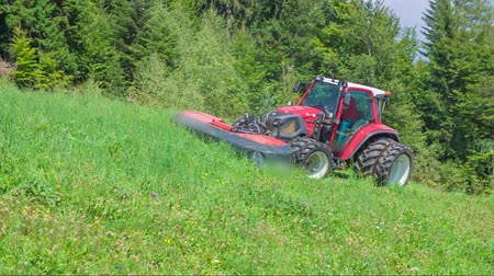 hay mowing : A tractor is driving on the hill and the farmer is cutting grass with grass cutting machinery. The day is sunny and beautiful. Stock Footage