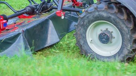 hay mowing : A tractor is driving on the green grass and he is connected to the grass cutting machine. Stock Footage