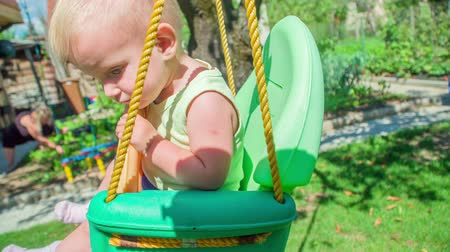 descobrir : Tired little baby girl is rocking on a colourful plastic swing while a woman is  working in a garden.