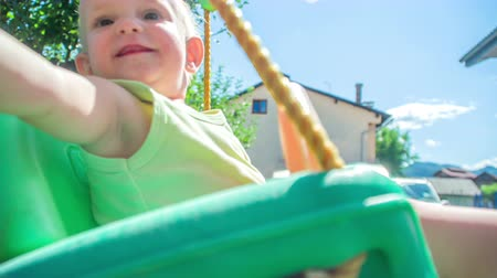 focus on foreground : Curious toddler is rocking on a colourful swing and trying to grab a camera. Stock Footage