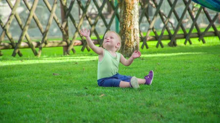 descobrir : Cute baby girl sitting on the lawn and trying to grab something on a hot summer day.