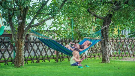 foco no primeiro plano : Young mother and her son relaxing and swinging in hammock while little cute baby girl sits on the lawn and plays with pink flip flops.