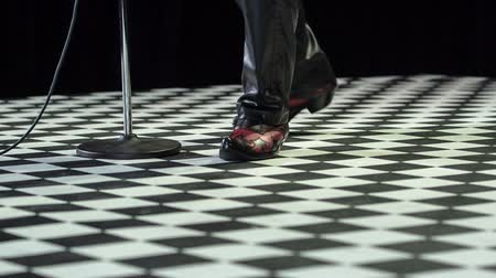ゴージャス : Atractive male singer dressed in black trousers and wearing special boots slowly walking towards the microphone.