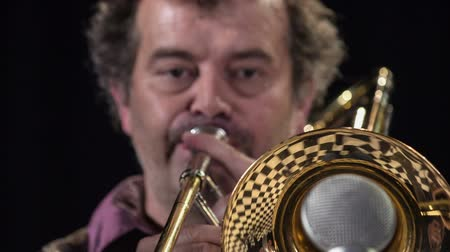 bas : Male trumpetist with curly hair playing trombone nad performs on the stage.