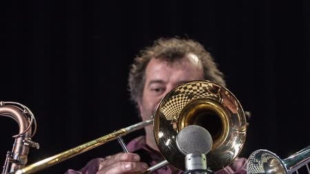 trombeta : Elderly male trumpetist with curly hair performing on the stage and entertain the audience. Stock Footage