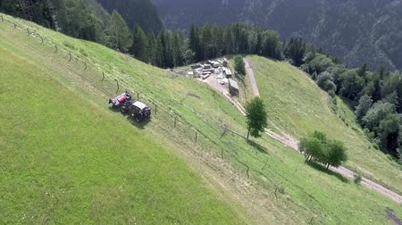 тюк : A tractor is carefully driving uphill when it is preparing hay in the summer. There is a beautiful farm on the foot of the hill. Стоковые видеозаписи