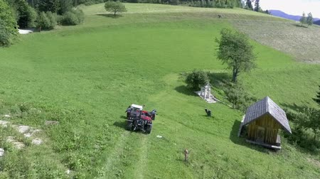 bales : A red tractor is leaving the farm and is approaching the field of hay. Its a nice summer day.