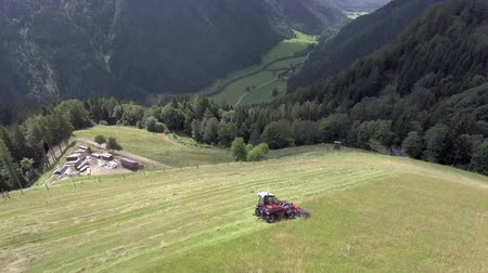 тюк : A farmer is preparing hay on a steep hill. A farm is seen on the foot of the hill. Its a sunny day. Aerial shot.