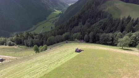 bales : A farmer needs to cut grass and prepare hay on a huge meadow up in te mountains. Aerial shot. Its summer time.