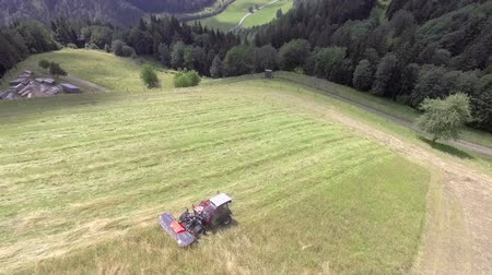 тюк : A farmer is cutting grass with a special machinery and is pulling it behind a tractor. He has done most of the work already. Стоковые видеозаписи