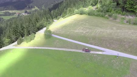 bitki : A small red tractor is driving uphill and is approaching the main country road. Aerial shot. Its a beautiful summer day. Stok Video
