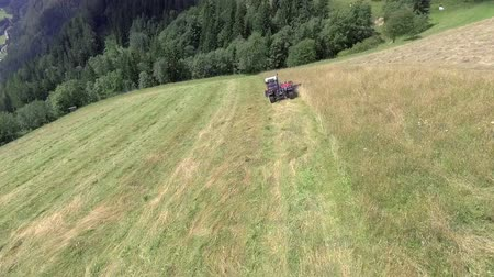 bales : A tractor is cutting grass with a special machinery on a steep mountain. The day is sunny and warm. Stock Footage