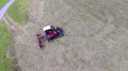 hay fields : The parts on the agricultural machinery start moving and the tractor is still standing still. Aerial shot.