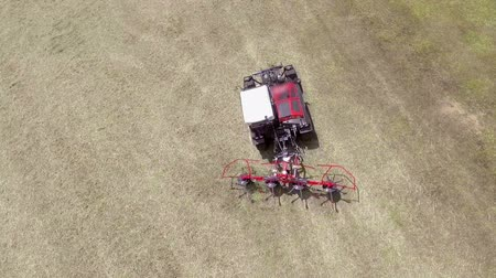bales : A huge tractor is pulling agricultural machinery behind it and is preparing hay. Its summer time. Aerial shot.