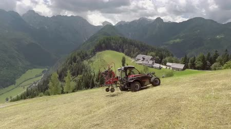 hay fields : A tractor is standing on a hill and it slowly starts moving backwards. A sunny summer day. Aerial shot. Stock Footage