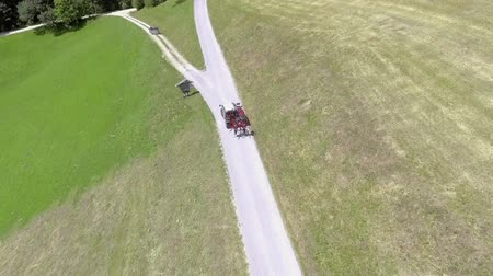 bales : A road is leading into two different directions. Aerial shot. Two vehicles are driving there.