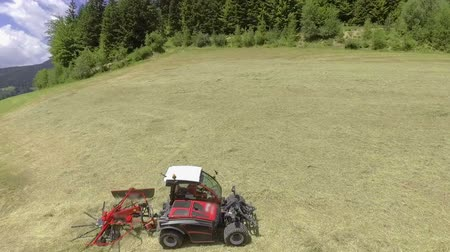 hay bale : A red tractor starts moving and preparing hay. Its a hot summer day. Aerial shot.