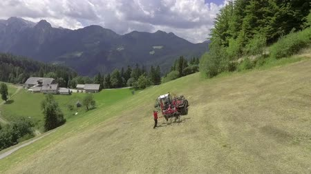 balla : A tractor is standing still in the middle of a hill and a man is standing outside and is fixing something. Aerial shot.
