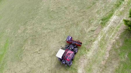 тюк : Agricultural machinery is turning around really fast when preparing hay on the hills. Aerial shot.