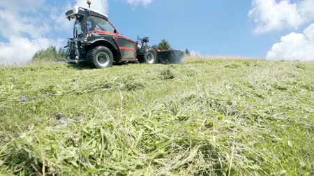 döner : Farmers are cutting grass with the grass cutting machinery on a nice summer day. Stok Video