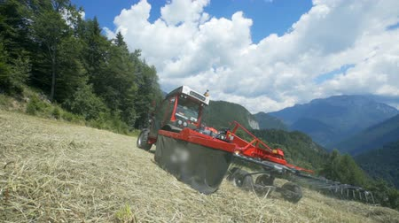 hay mowing : A tractor is driving on a steep hill very carefully. The day is sunny and wonderful. Stock Footage