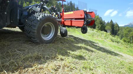 döner : A tractor is standing still in the middle of a hill on a hot summer day. The farmers are preparing hay in this period of the season.
