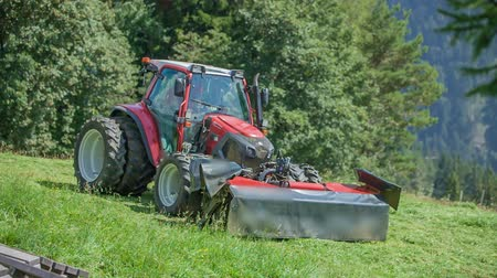 mow : A grass cutting machinery lifts up and a tractor starts driving downhill. A farmer finished cutting grass. Its summer time. Stock Footage