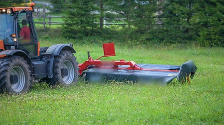 mow : A grass cutting machinery slowly lowers down and a farmer is ready to go and start cutting grass. Its summer time.