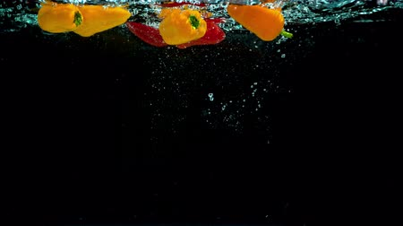 fresh produce : Raw and organic red and orange peppers elegantly fall into pot of fresh crystal clear water. Stock Footage