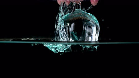 očistit : Young male slowly takes the glass full of water out of the crystal clear water. That makes remarkable bubbles.